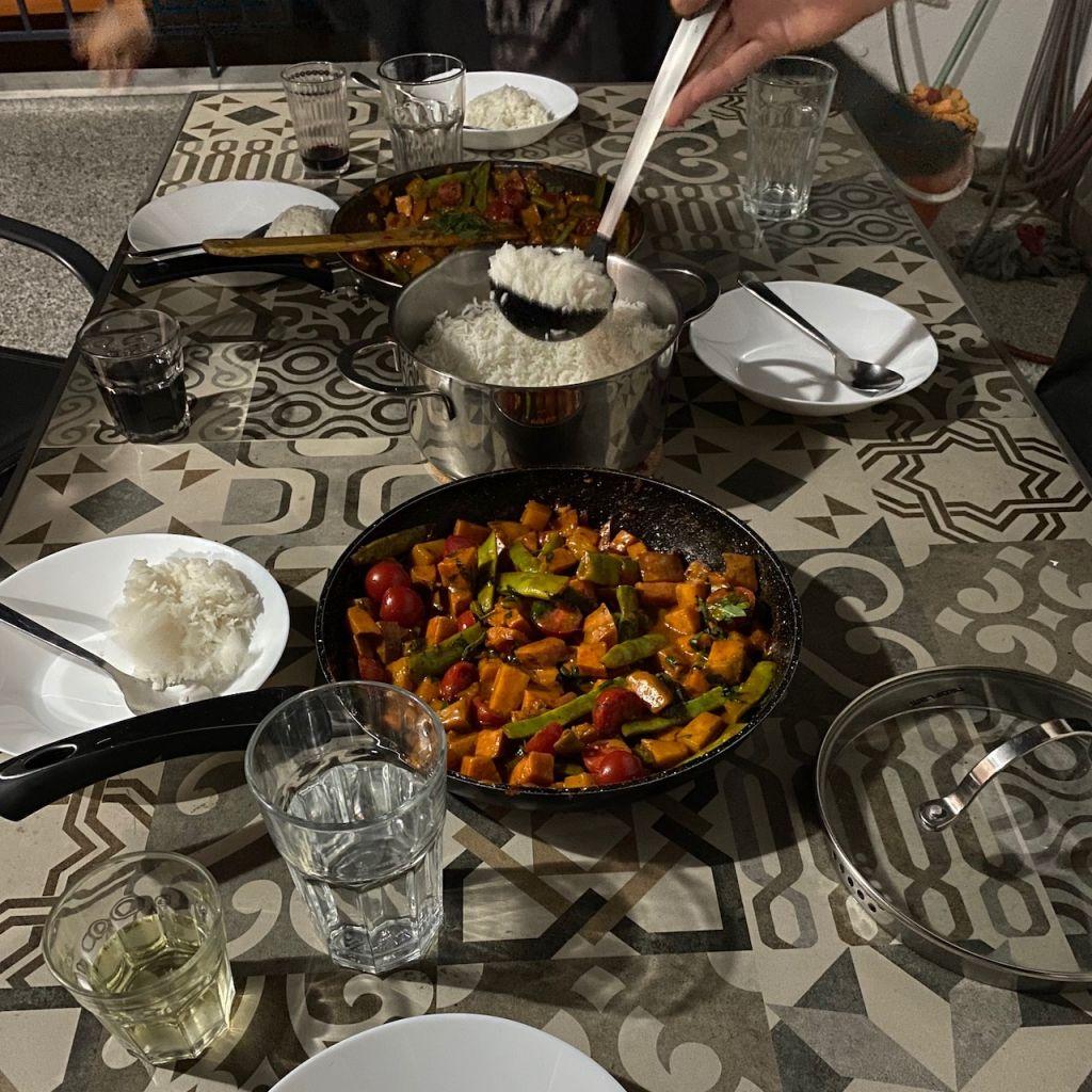 Auf dem Foto sieht man einen Tisch, auf welchem zwei Pfannen mit Gemüsecurry stehen. Zwischen den beiden Pfannen steht ein Topf voll mit Reis, aus welchem auf fünf Tellern das Essen serviert wird.