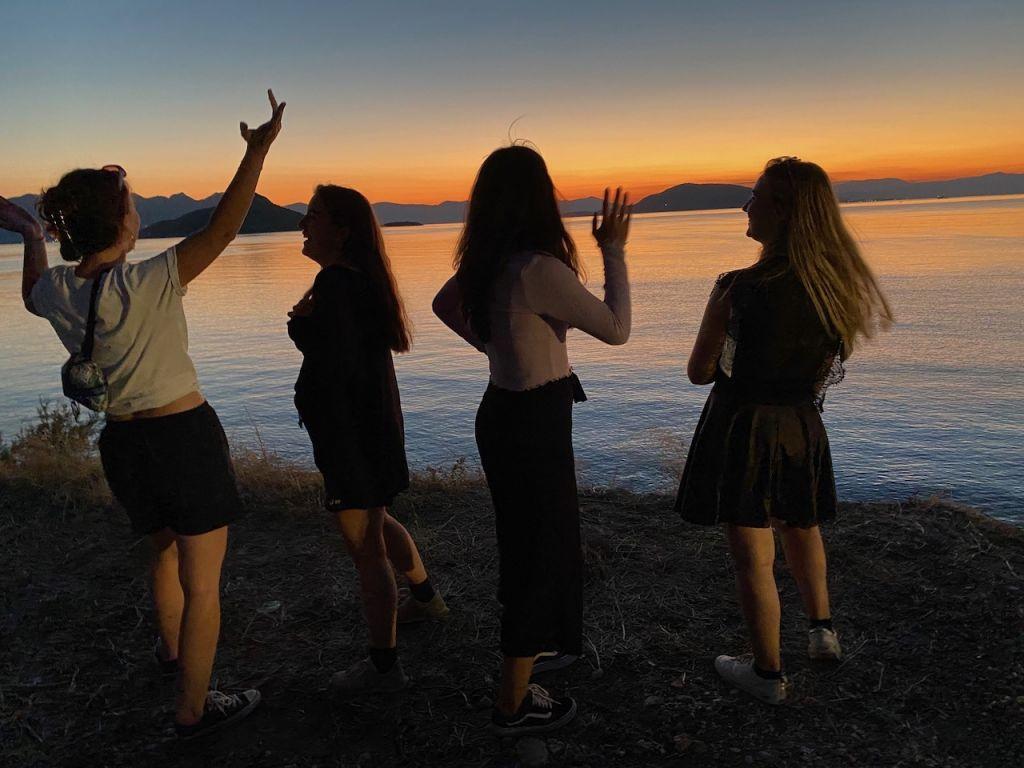 Im Hintergrund ist ein Sonnenuntergang am Meer zu sehen. Im Vordergrund stehen ich und drei Freundinnen, die gemeinsam auf das Meer schauen und lachen.