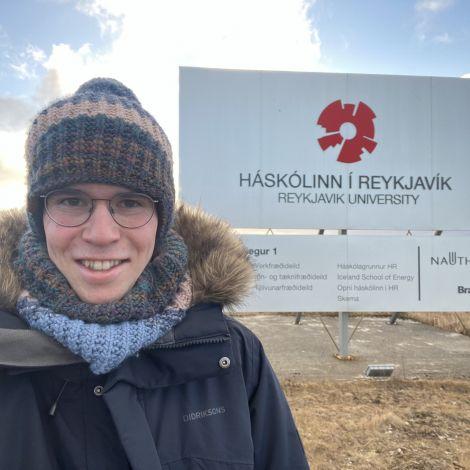 Ich vor einem Schild mit der Aufschrift Reykjavik University