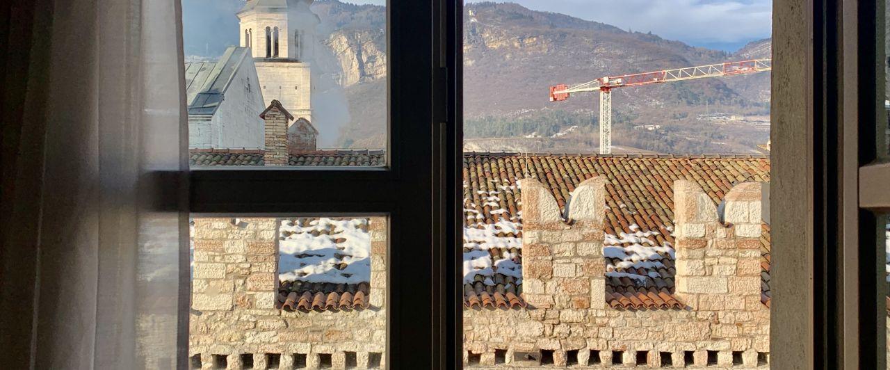 Ausblick aus dem Fenster auf Kirche und Berge in Italien