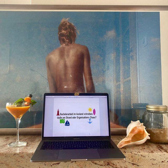 Vor einem gerahmten Bild steht ein Cocktailglas, mein Laptop, eine große Muschel und ein Einmachglas mit Sand.