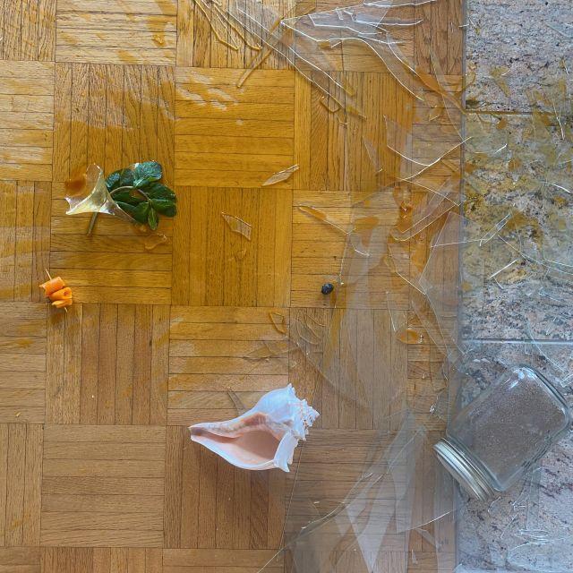 Auf dem Boden liegen Scherben, ein zerbrochenes Cocktailglas und ein orangener Saft. Eine große Muschel liegt dazwischen.