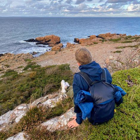 Benjamin sitzt auf einer Steinklippe am Meer