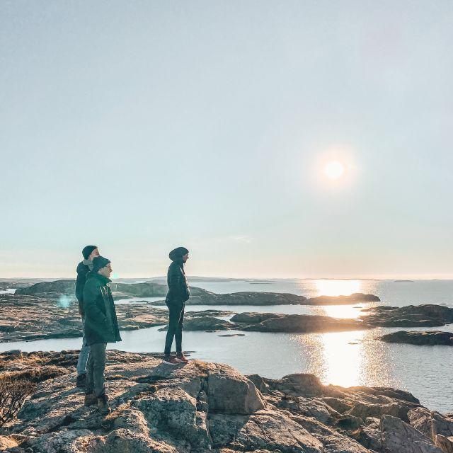 Meine drei Freunde stehen auf der felsigen Küste und schauen aufs Meer