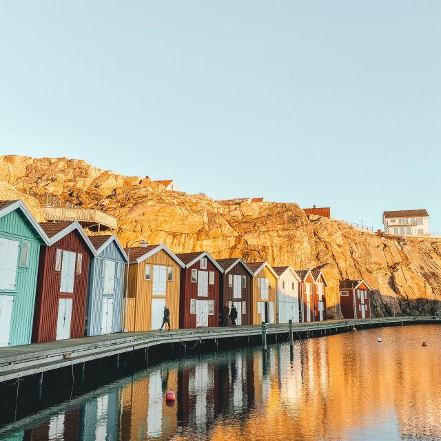 Bootslagerhäuser mit bunten Farben udn klassischen weißen Türen in einer Bucht in Smögen, Schweden.