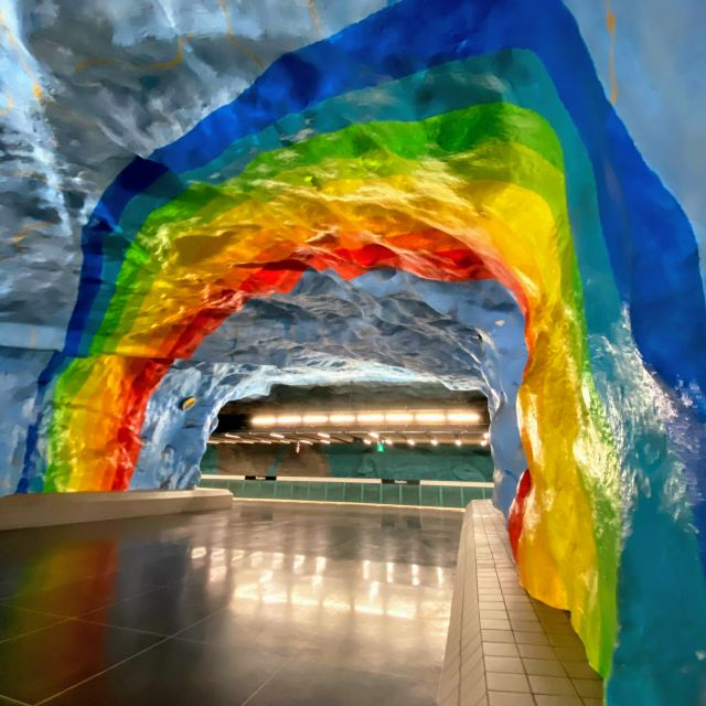 Eine Stockholmer UBahnstation ist mit einem blauen Himmel und einem Regenbogen gestaltet.
