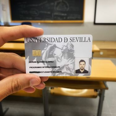 """Linke Hand hält eine weiße Karte mit der Aufschrift """"Universidad de Sevilla"""" und dem Foto eines hübschen jungen Mannes drauf, vor einer Tafel in einem Seminarraum."""