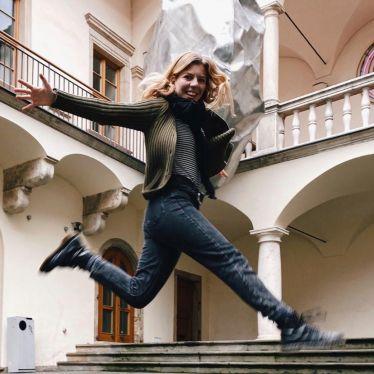 Eine Person, die in die Luft springt und in die Kamera lächelt
