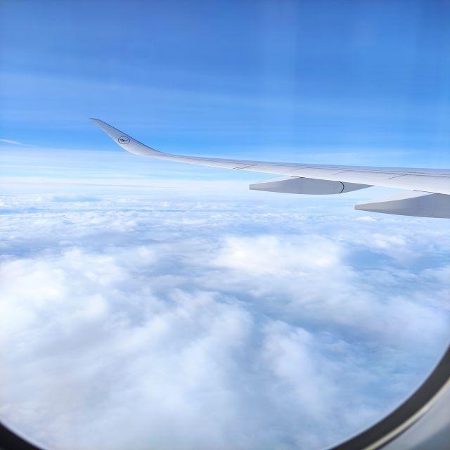 Blick aus Flugzeugfenster. Man sieht ein Wolkenmeer