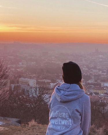 Bild von einem Panoramablick auf Brünn bei Sonnenuntergang mit einer Person, die den Sonnenuntergang anschaut. Die Person ist von hinten abgebildet.