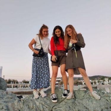 Im Vordergrund stehen meine beiden Freundinnen und ich auf einem kleinen Felsen. Ich trage ein rotes Oberteil mit einer kurzen Hose und meine Freundinnen tragen beide Kleider. Im Hintergrund ist der Himmel und Häuser zu erkennen.