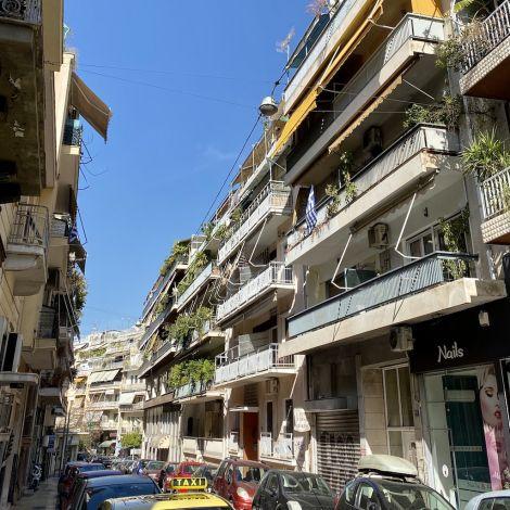 Auf dem Bild sind mehrstöckige Wohnhäuser zu sehen, von denen jeweils ein Balkon hervorragt. Von den Balkonen ranken viele grüne Pflanzen herunter. Im Hintergrund ist blauer Himmel zu sehen. Das Sonnenlicht fällt fasst senkrecht in die Straße ein.