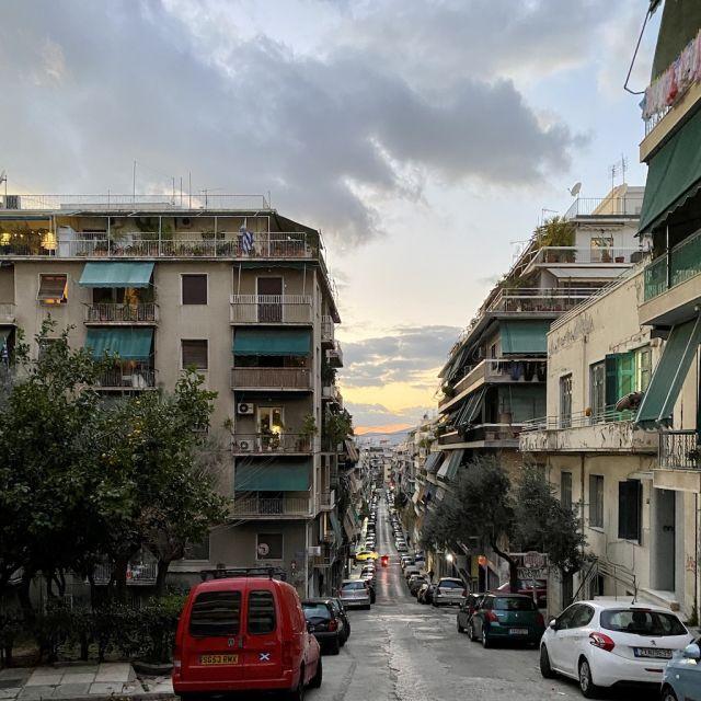 Auf dem Bild erkennt man eine lange Straße, die ziemlich steil bergab verläuft. Der Himmel ist von der untergehenden Sonne gezeichnet und es ziehen einige Wolken vorbei. Links und rechts der Straße befinden sich Wohnhäuser mit Balkonen und Dachterrassen.