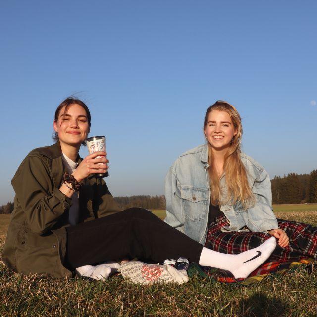 Meine Freundin Heli und ich sitzen auf der Wiese und gönnen uns eine Pause mit Tee und Schokolade.