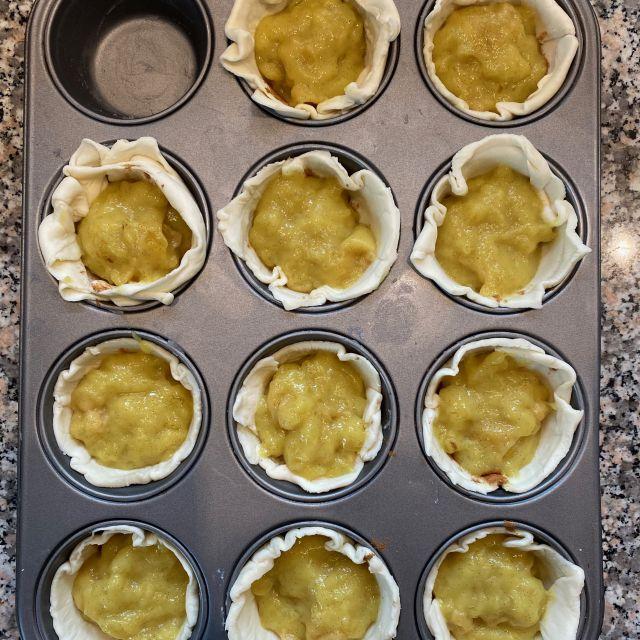 Die gelbe Puddingfüllung befindet sich in den Blätterteigförmchen und ist bereit für den Ofen.