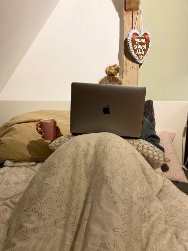 Mit dem Laptop auf dem Schoß und der Teetasse in der Hand liege ich im Bett.