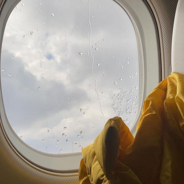Der Blick aus dem Flugzeugfenster zeigt nur eine dicke, graue Wolkendecke.