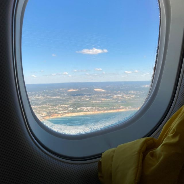 Blick aus dem Flugzeugfenster: blaues Meer, Sandstrand und grüne Flächen im Hintergrund