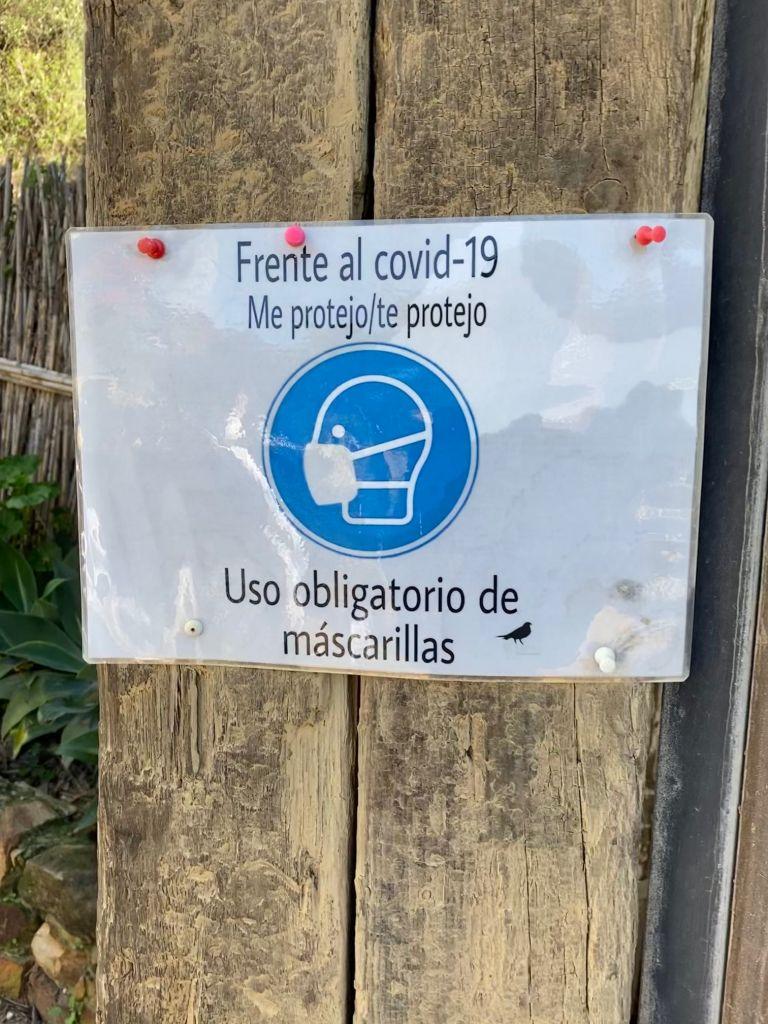 """Ein laminierter Zettel auf Holz gepinnt mit einem Piktogramm eines Maske-tragenden Kopfes weiß auf blauem Grund. Dazu auf Spanisch: """"Frente al covid-19. Me protejo/te protejo. Uso obligatorio de mascarillas."""""""