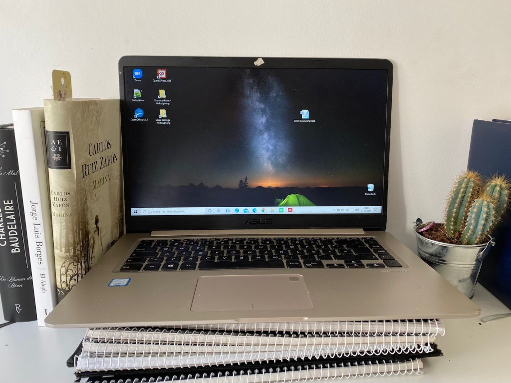 Ein geöffneter Laptop auf drei College-Blöcken mit dunklem Hintergrundbildschirm, links zwei Bücher.