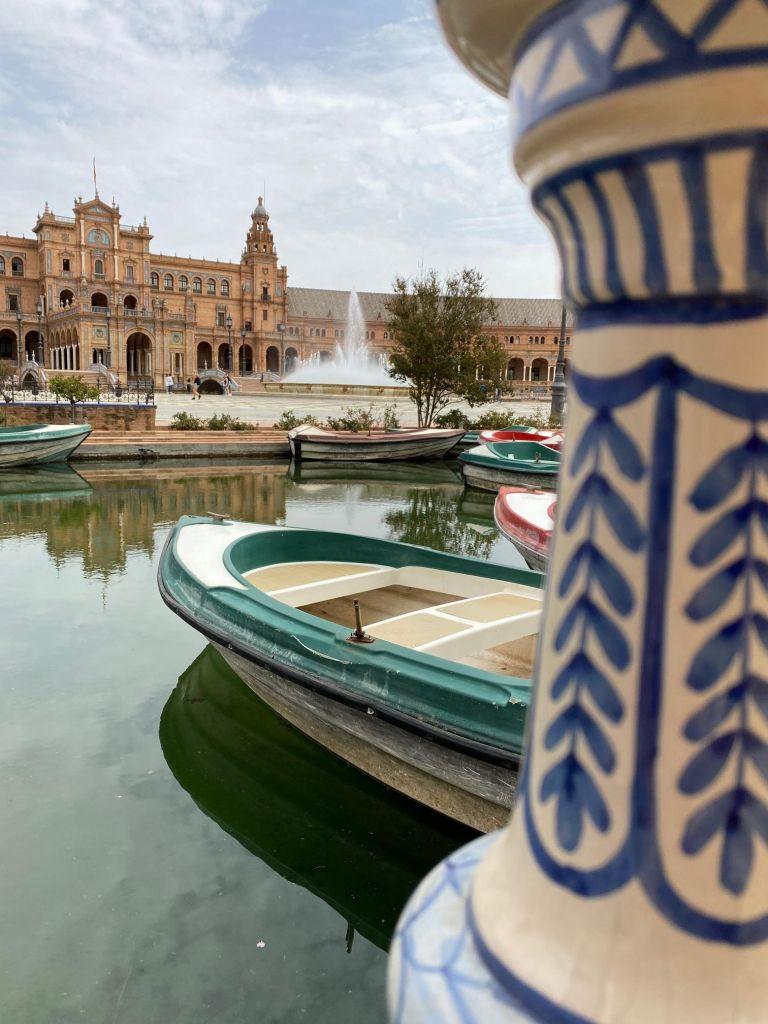 Eine weiße Säule mit blauer Zier, dahinter ein grünes Boot auf einem kleinen Teich und dahinter ein imposantes Gebäude und ein Springbrunnen.