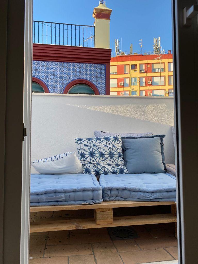 Blick aus einem Fenster auf einen Balkon, auf dem Paletten stehen und darüber blaue Kissen, dahinter blauer Himmel.