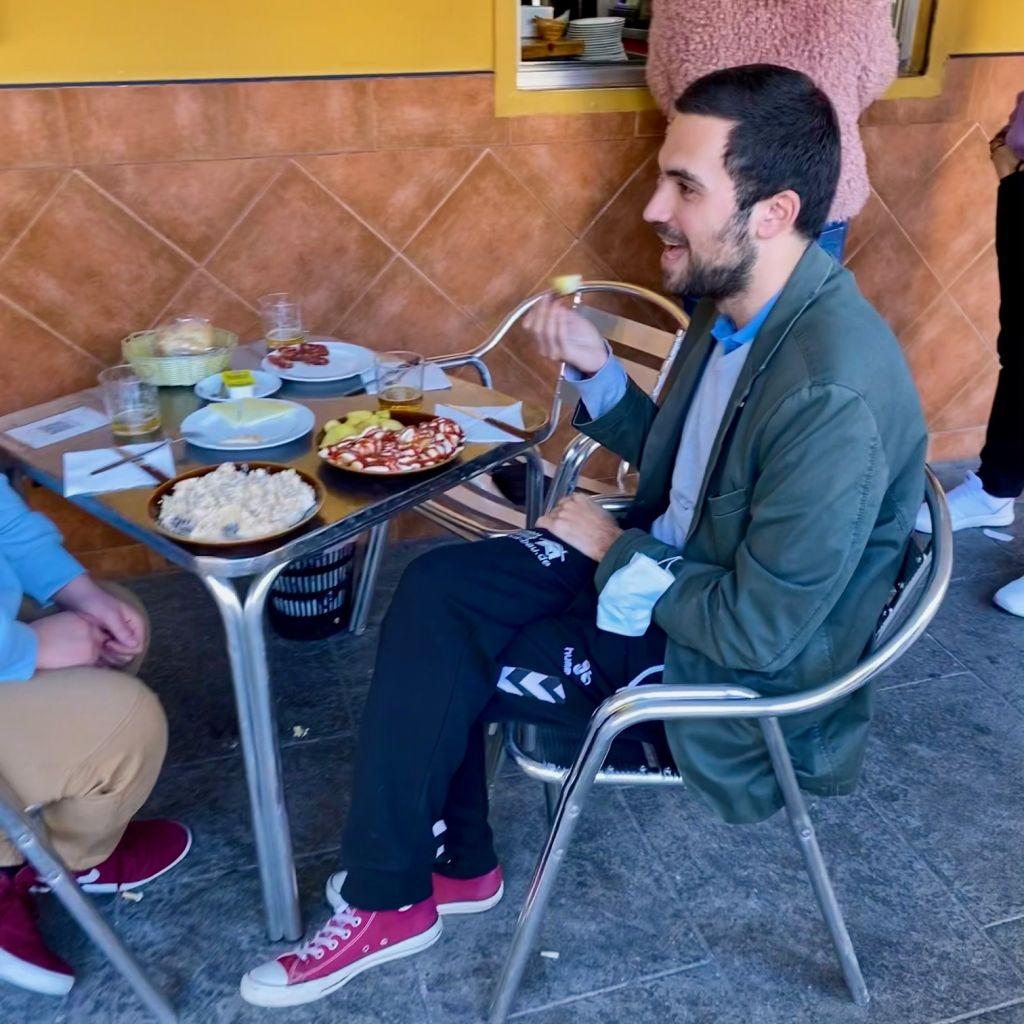 Junger Mann sitzt mit übereinandergeschlagenen Beinen am Tisch im Außenbereich einer Bar. Isst gerade eine Tapa, trägt Jogginghose, rote Chucks und ein graues Sakko.