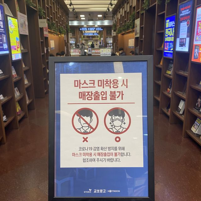 Ein Schild in einem Buchladen, das an die Maskenpflicht erinnern soll.