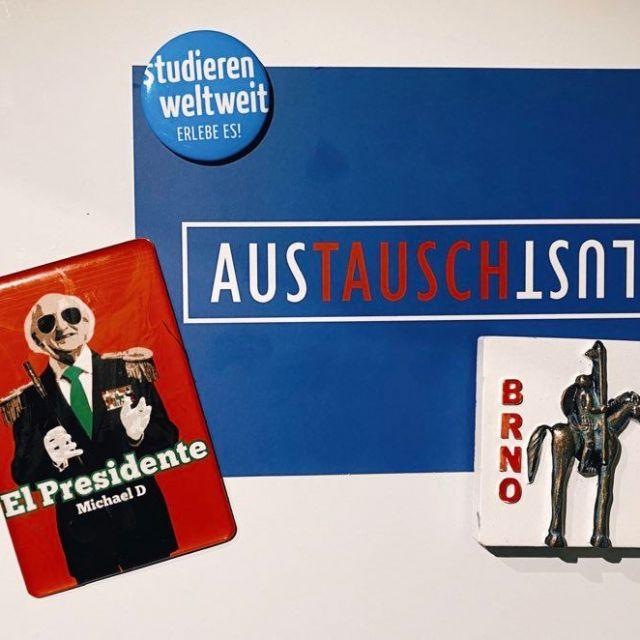 Eine Postkarte mit der Aufschrift Austauschlust und drei Magnete (studieren weltweit, Michael Higgins und Pferdestatue aus Brünn), die an einer Magnetwand hängen