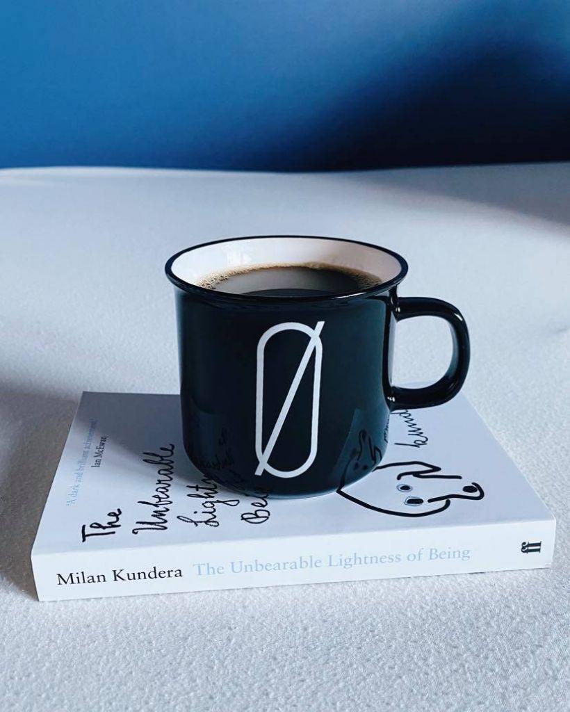 Eine schwarze Tasse, die auf einem Buch steht