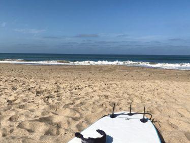 Ein Surfbrett liegt im Sand und im Hintergrund brechen sich die Wellen.