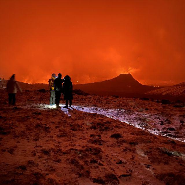 Ein Vulkankegel umbeben von roten Wolken.