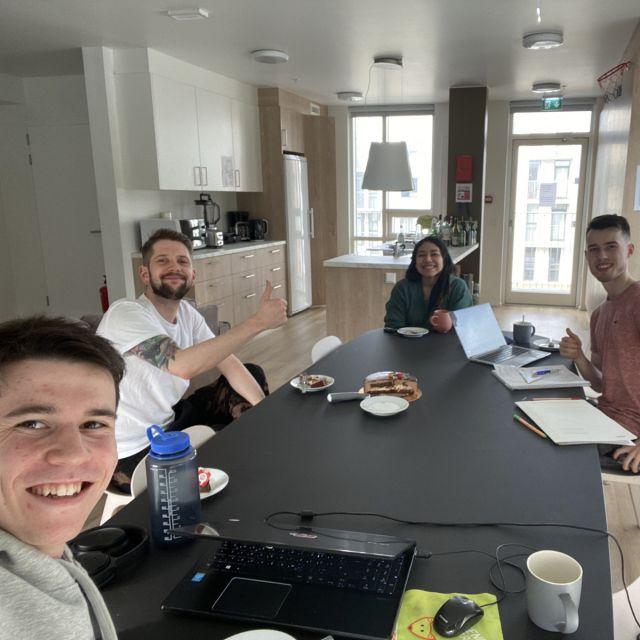 Vier personen in der Gemeinschaftsküche eines Studentenwohnheims