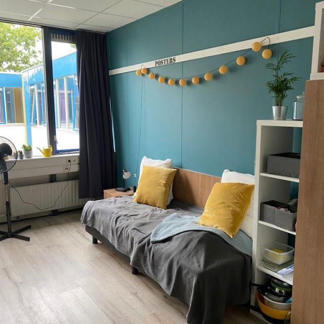 Man sieht die eine Seite meines Zimmers. Die Wand ist blau an ihr habe ich eine gelbe Lichterkette gehangen. auf dem Bett liegt eine Tagesdecke und vier Kissen. Die Tagesdecke ist grau, die Wolldecke blau, die Kissen weiß und gelb. Rechts vom Schrank steht ein Ikeaschrank in weiß, dort sind meine Küchenutensilien verstaut.