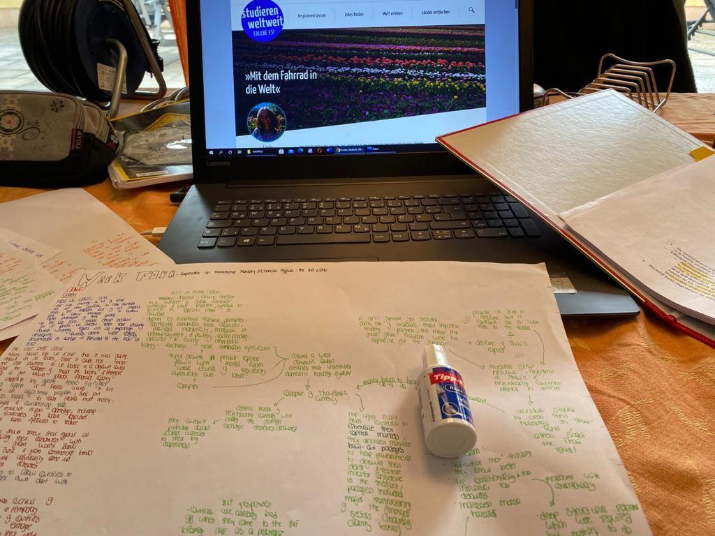 Man sieht meinen Laptop. Geöffnet ist meine Seite bei studieren weltweit. Vor meinem Laptop liegt alllerlei Papierkrams.