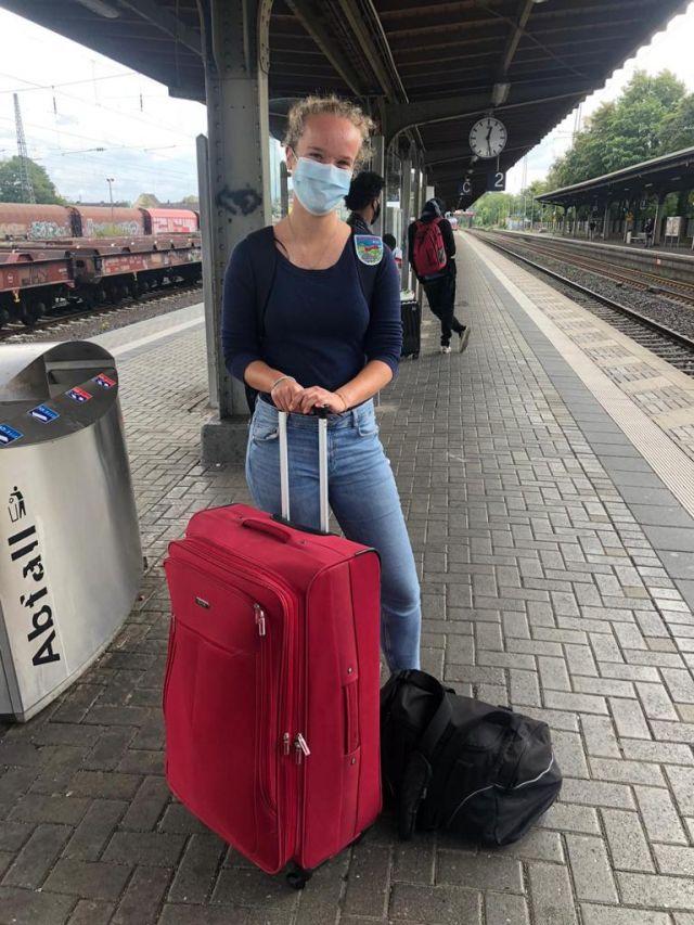 Man sieht auf diesem Bild mich, ein Mädchen mit Locken und einer Maske im Gesicht. Ich stehe am Bahnhof mit einem roten Koffer und einem Rucksack und bin bereit, nach Groningen zu fahren.