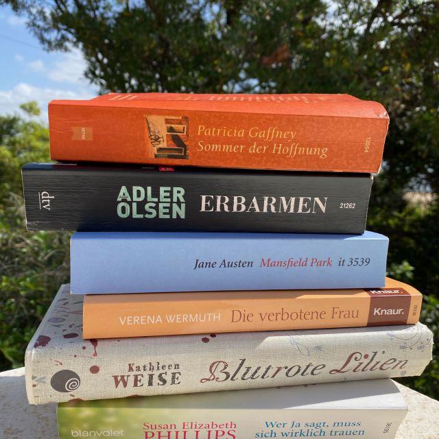 Ein hoher Stapel Bücher steht draußen in der Sonne und im Hintergrund sind grüne Bäume zu erkennen.