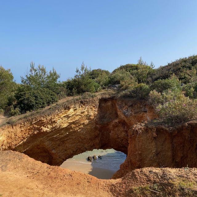 Ein Loch befindet sich im Felsen und gibt den Ausblick zum Strand frei.
