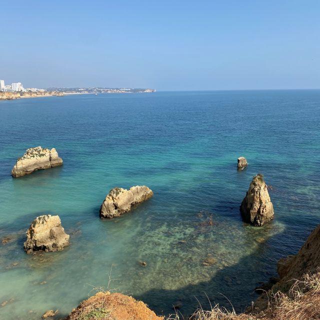 Ausblick über türkisfarbenes Meer mit felsigen Steinen.