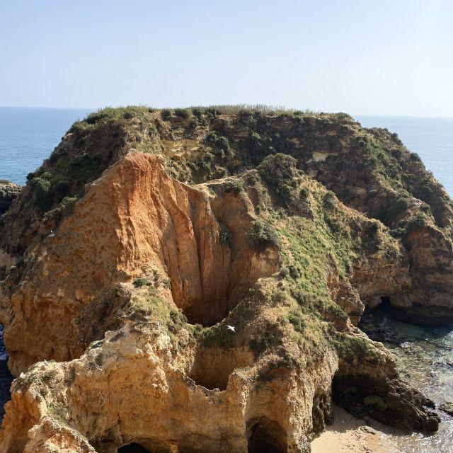 Ein großer Felsen, mit vielen Gängen und Höhlen teilt den Strand und ragt ins Meer hinaus.