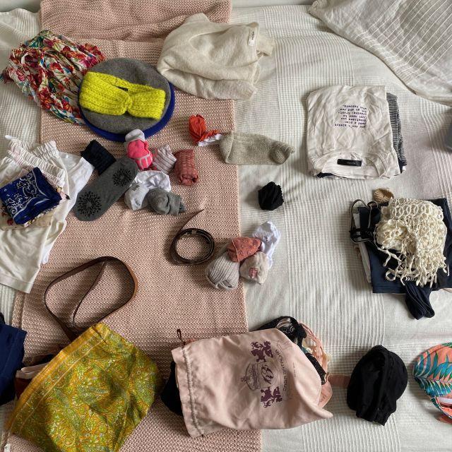 Alle möglichen Klamotten liegen auf dem Bett verteilt.
