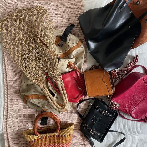 Handtaschen liegen verteilt auf dem Bett.