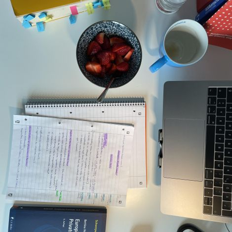 Mein Schreibtisch während einer Vorlesung samt Snacks, Laptop und Lehrmaterialien