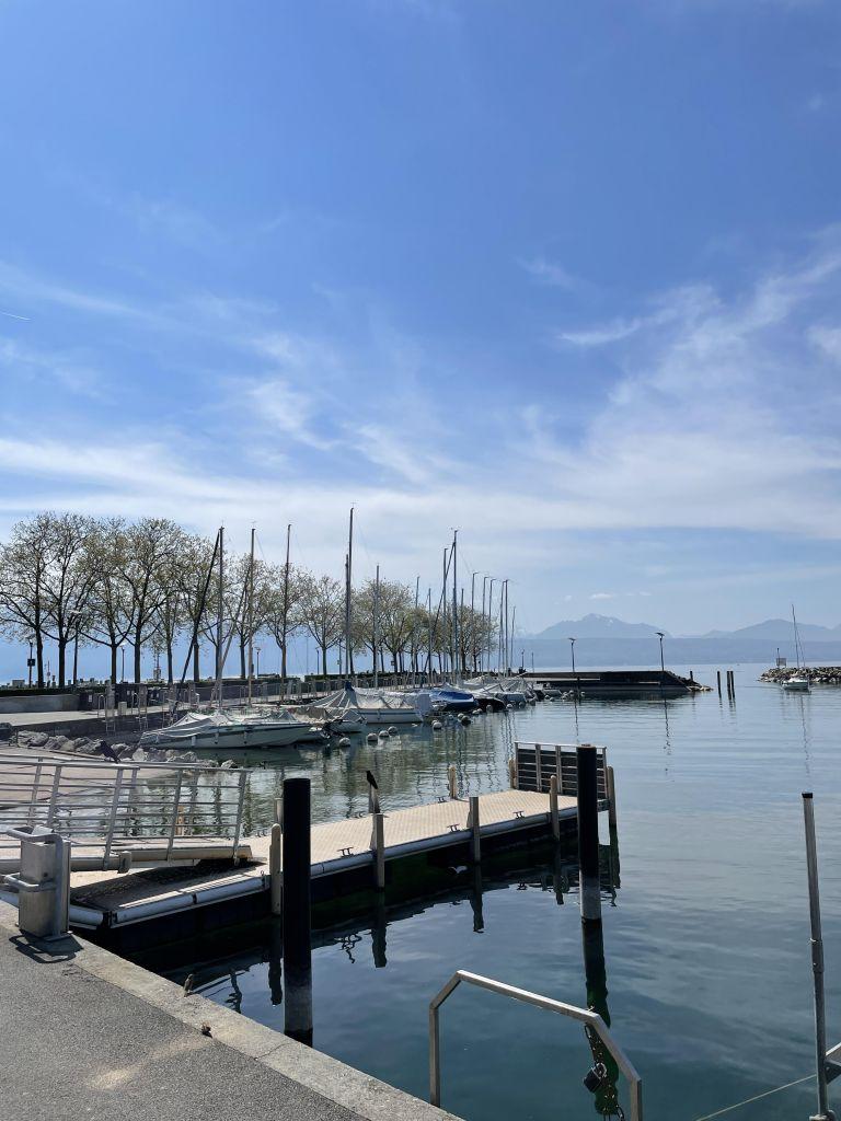 im Vordergrund Boote, im Hintergrund der Genfersee