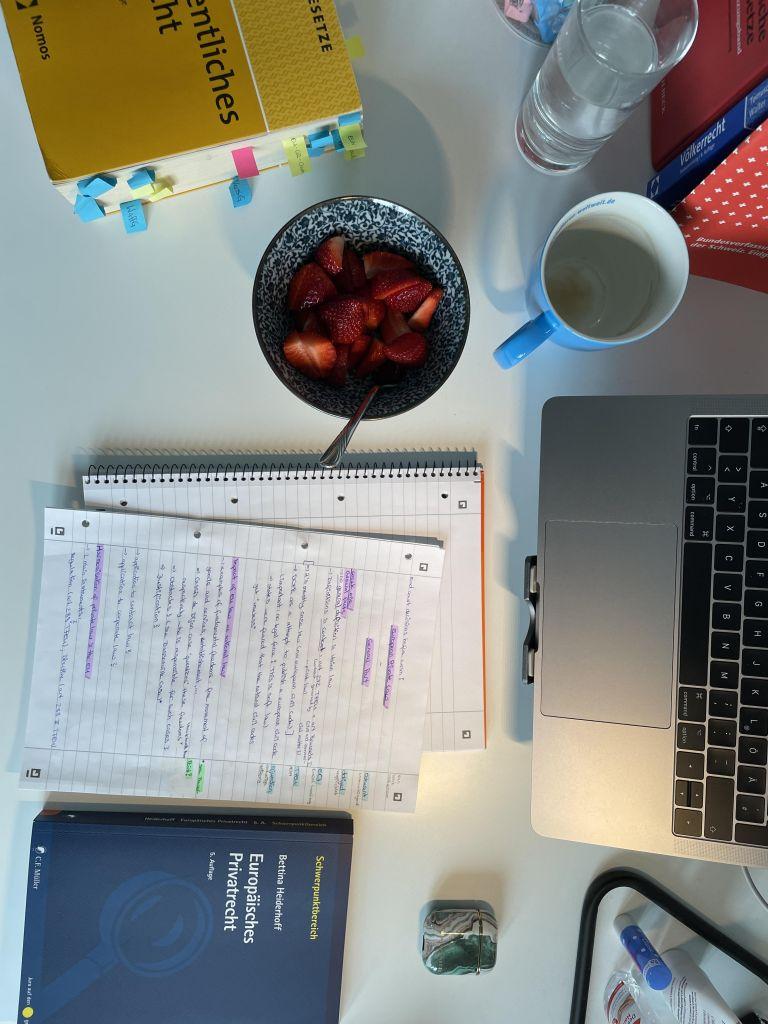 Man sieht meinen Schreibtisch im Homeoffice mit Vorlesungsnotizen, Lehrbücher und Gesetzestexten, Snacks und meinem Laptop
