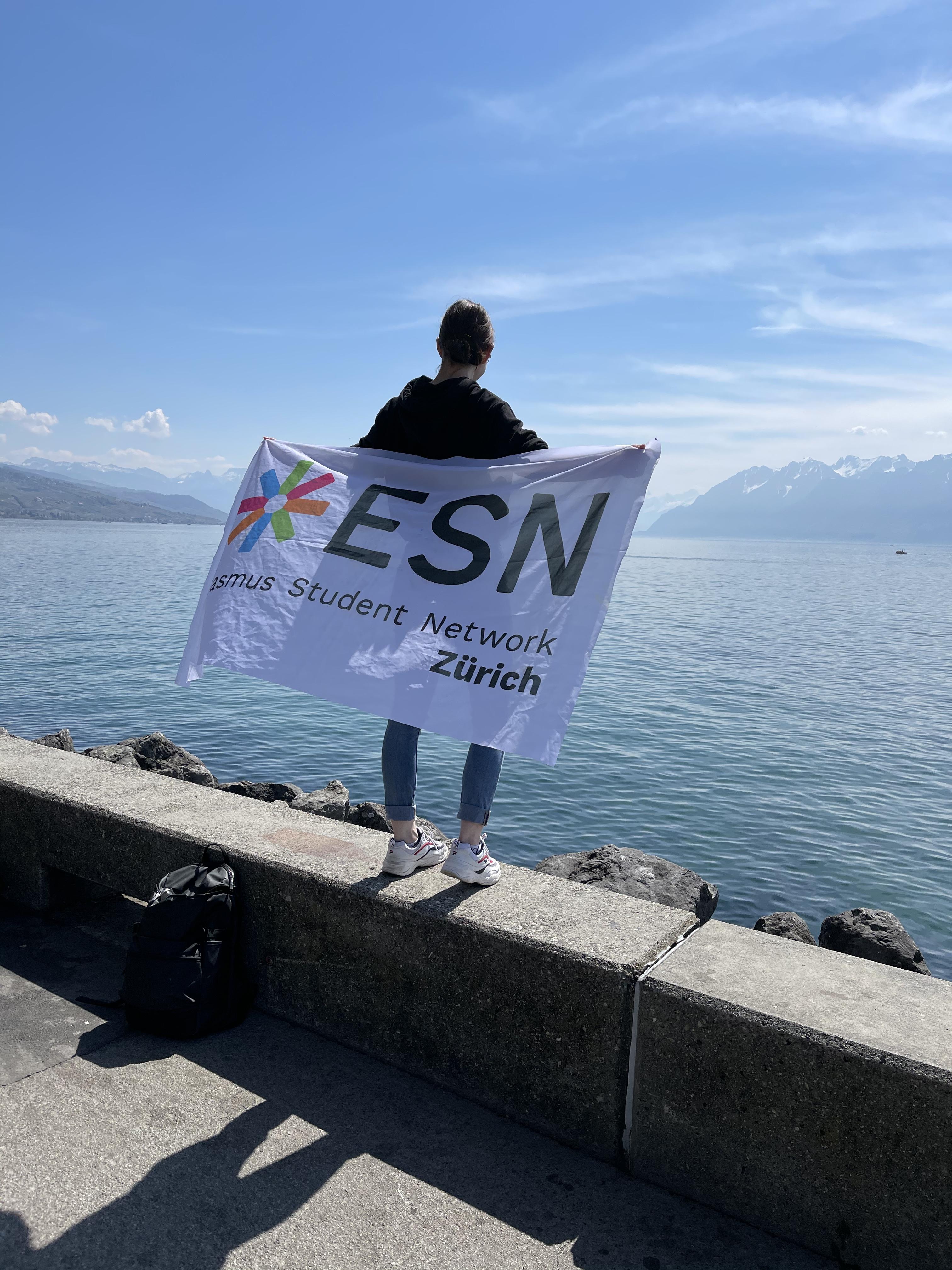 Ich stehe am Genfersee und halte die ESN Zürich Flagge