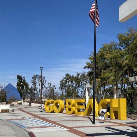 USA Flagge und im Hintergrund das Motto der Cal State Long Beach