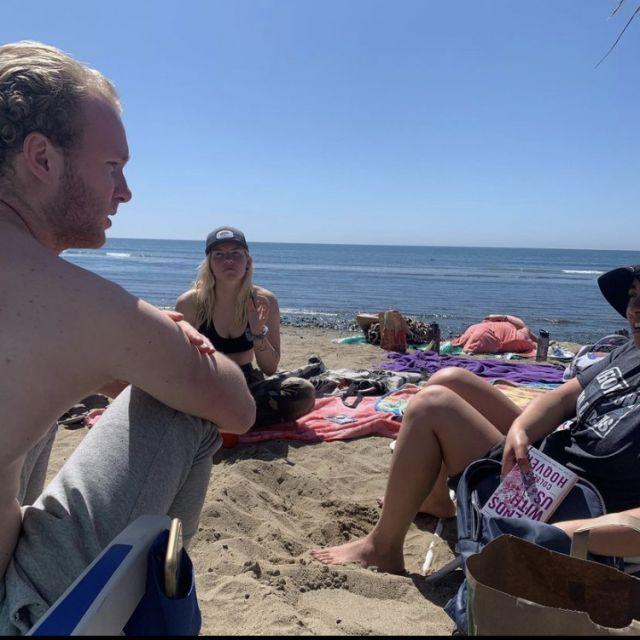 Menschen unterhalten sich und sitzen auf Sand.