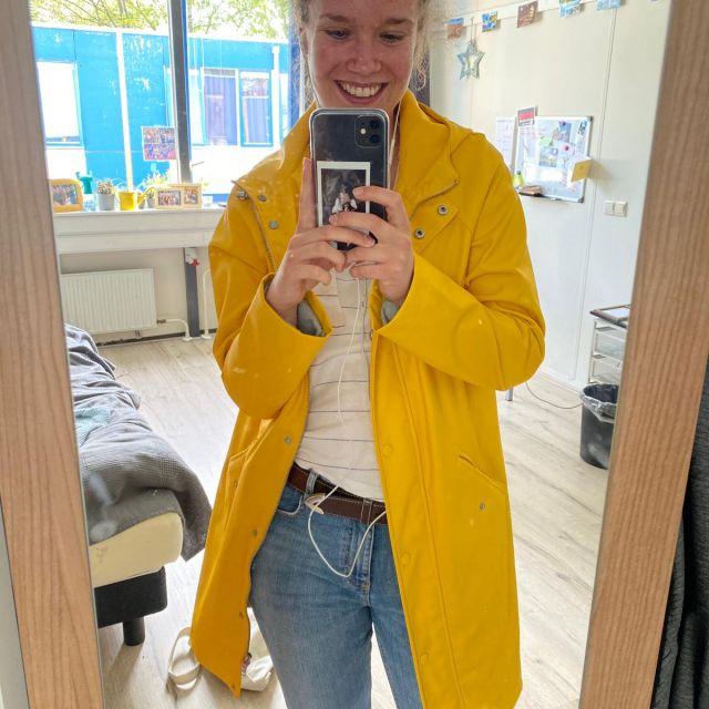 Man sieht mich vor einem Spiegel. Ich trage eine gelbe Regenjacke.