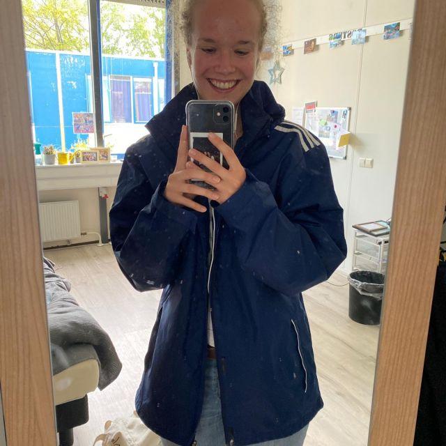 Man sieht mich in einer blauen Regenjacke.